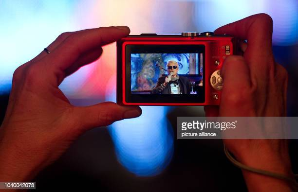 A fan takes pictures of German crooner Heino performing during a show at the NDRpublic broadcasting house in Hamburg Germany 01 February 2013 Heino...
