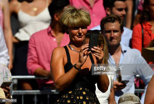 A fan takes pictures of Rafael Nadal of Spain against Lucas Pouille of France during the Aspall Tennis Classic at Hurlingham on June 29 2018 in...