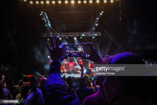 A fan taking a picture with her phone during an AAA World Wide Wrestling match on November 16 2018 in Bogota Colombia