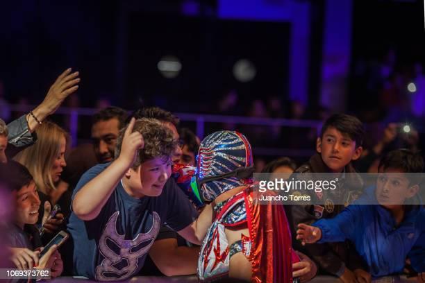 A fan talks to wrestler Aerostar AAA during an AAA World Wide Wrestling match on November 16 2018 in Bogota Colombia