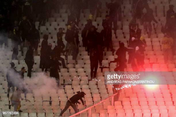 A fan throws a flare during the Greek Cup final football match between AEK FC and PAOK Salonika at the Olympic stadium in Athens on May 12 2018