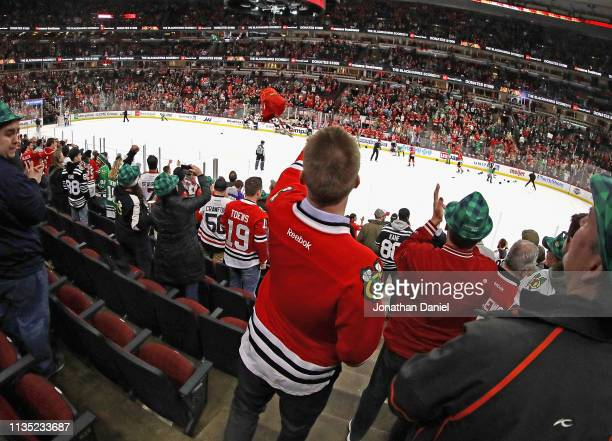 Fan throws his hat onto the ice after Brendan Perlini of the Chicago Blackhawks scored his third goal of the game against the Arizona Coyotes with...