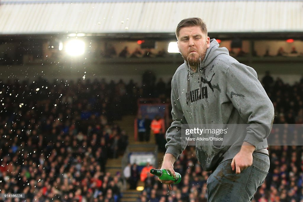 A fan throws lager over his face as he runs onto the pitch during the Premier League match between Crystal Palace and Newcastle United at Selhurst Park on February 4, 2018 in London, England.