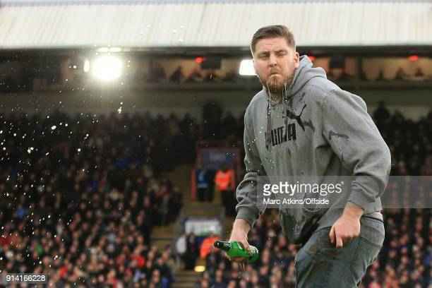 A fan throws lager over his face as he runs onto the pitch during the Premier League match between Crystal Palace and Newcastle United at Selhurst...