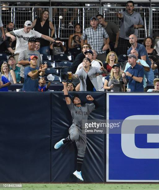 A fan touches Jon Jay of the Arizona Diamondbacks glove as he leaps for a home run hit by Eric Hosmer of the San Diego Padres during the fifth inning...