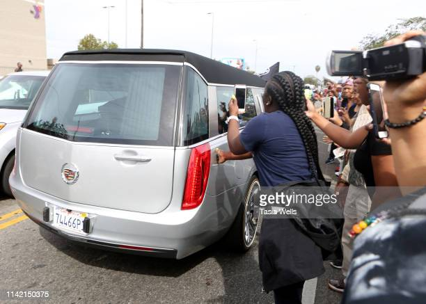 A fan touches the hearse carrying Nipsy Hussle's body during his Funeral Procession as it passes through Vermont Ave on Crenshaw Blvd on April 11...