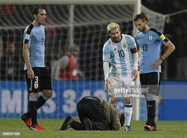 TOPSHOT A fan tries to kiss the feet of Argentina's Lionel Messi during the Russia 2018 World Cup qualifier football match against Uruguay in Mendoza...