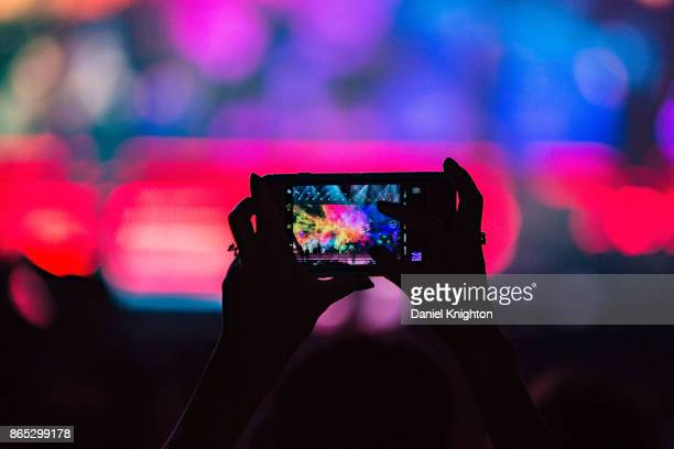 A fan uses a cell phone to take a photo of Enrique Iglesias performing on stage at Valley View Casino Center on October 22 2017 in San Diego...