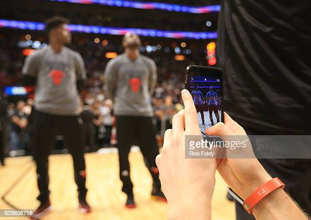 A fan uses a cell phone to take a picture of Jimmy Butler and Dwyane Wade of the Chicago Bulls before the game against the Miami Heat at American...