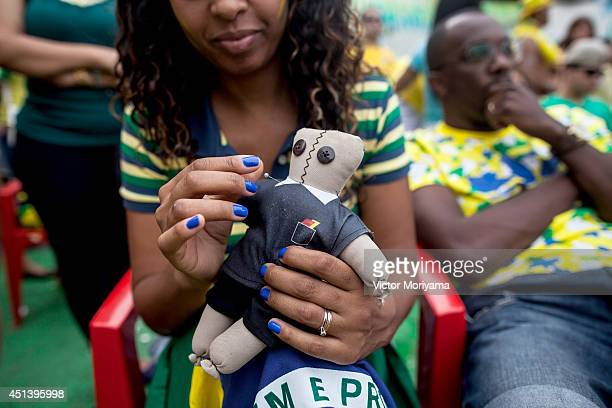 A fan uses a voodoo doll of Howard Webb while watching the Round of 16 match between Brazil and Chile during the 2014 FIFA World Cup in Bela Vista on...