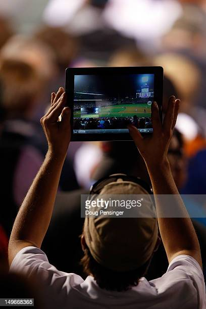 A fan uses an Apple iPad to take a photo of the game between the St Louis Cardinals and the Colorado Rockies at Coors Field on August 1 2012 in...