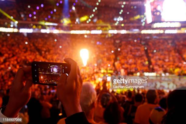 A fan uses his iPhone to take a photo of player introductions prior to Game Four of the 2019 NBA Finals between the Golden State Warriors and the...