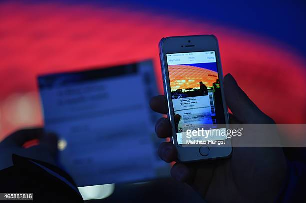 A fan uses his mobile phone to take a photograph of his match ticket prior to the UEFA Champions League Round of 16 second leg match between FC...