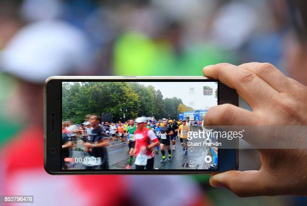 A fan videos runners at the start of the Berlin marathon on September 24 2017 in Berlin Germany