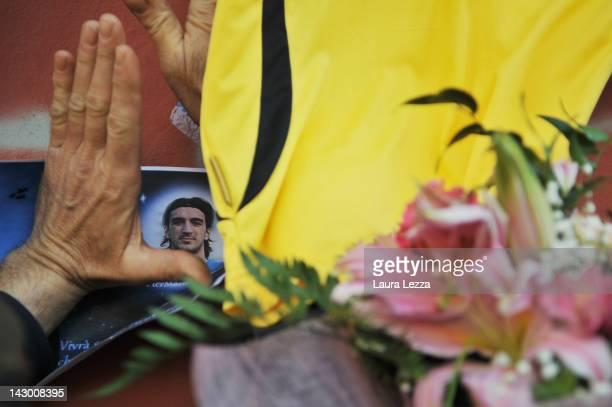 Fan views a photograph of Piermario Morosini amonst floral tributes outside Armando Picchi Stadium, where the coffin of the late AS Livorno...