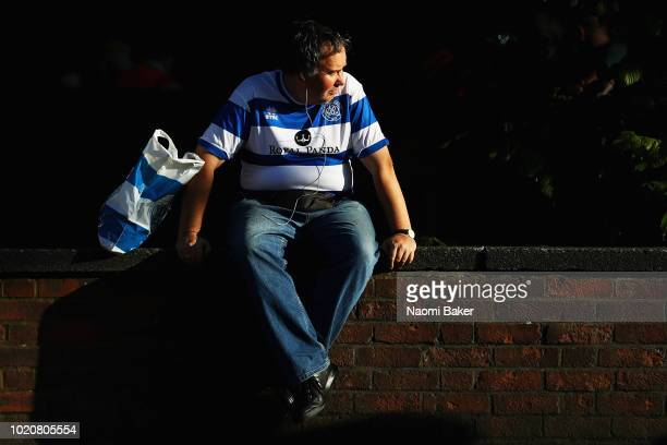 A fan reads a programme as he waits outside the stadium prior to the Sky Bet Championship match between Queens Park Rangers and Bristol City at...