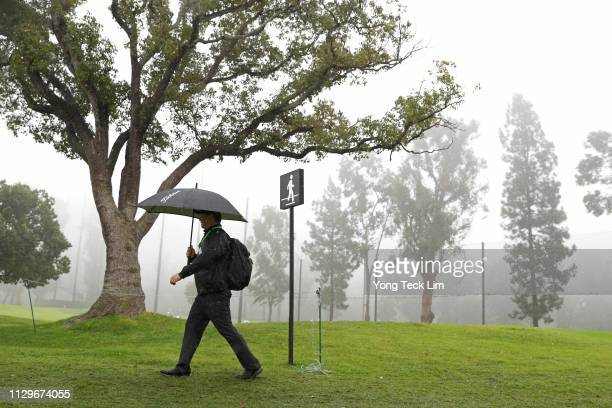 Fan walks along the course as play is suspended due to rain during the first round of the Genesis Open at Riviera Country Club on February 14, 2019...