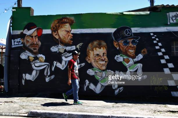 A fan walks past a mural of Fernando Alonso of Spain and McLaren Honda Jenson Button of Great Britain and McLaren Honda 2016 F1 World Drivers...