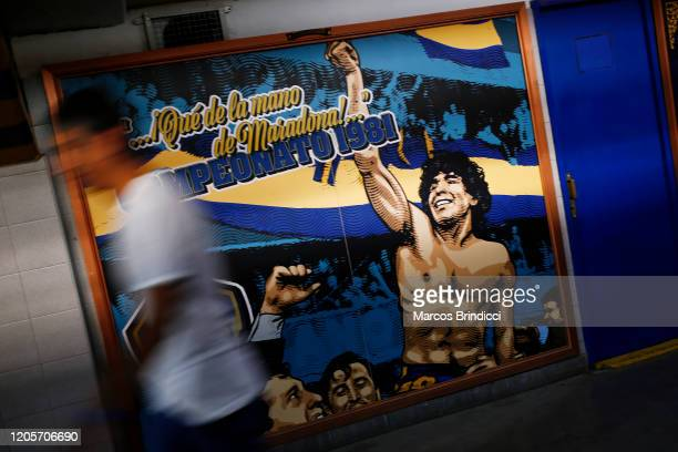 A fan walks past a mural with an image of Diego Maradona former Boca Juniors player and coach of Gimnasia y Esgrima La Plata before a match between...