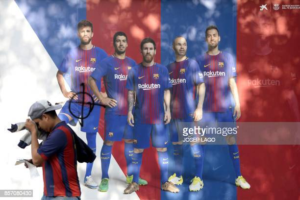 TOPSHOT A fan walks past a poster of Barcelona FC where the picture of defender Gerard Pique has been vandalised outside the club's Camp Nou stadium...