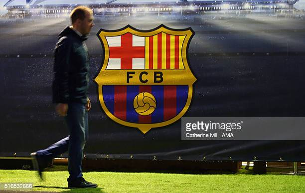 A fan walks past the FC Barcelona club badge before the UEFA Champions League match between FC Barcelona and Arsenal at Camp Nou on March 16 2016 in...