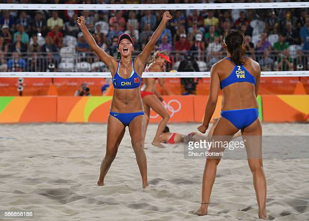 Fan Wang of China and Yuan Yue of China celebrate during the Women's Beach Volleyball preliminary round Pool C match against Isabelle Forrer and...