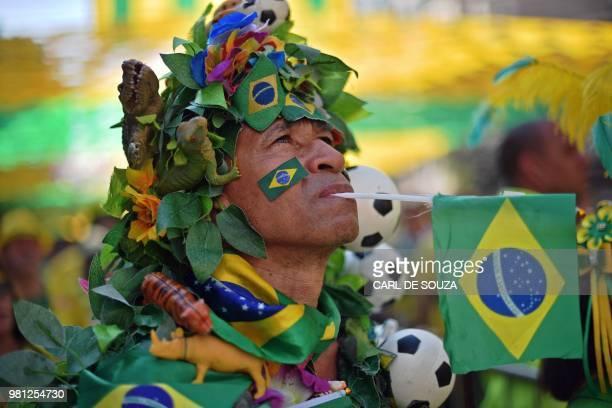 A fan watches a FIFA World Cup Russia 2018 football match between Brazil and Costa Rica on a giant screen at Alzirao neighborhood in Rio de Janeiro...