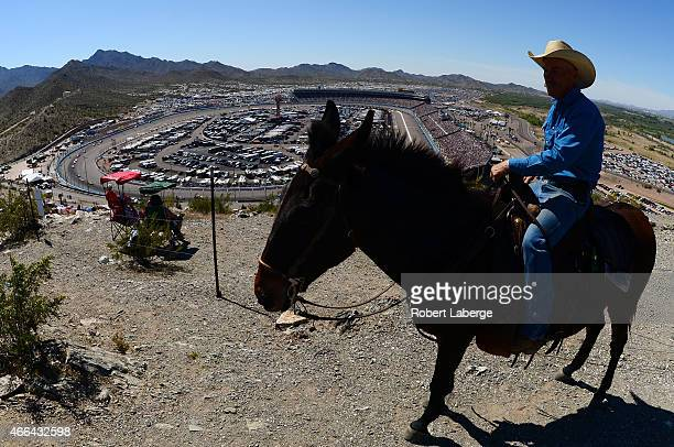 A fan watches cars race as he rides a horse during the NASCAR Sprint Cup Series CampingWorldcom 500 at Phoenix International Raceway on March 15 2015...