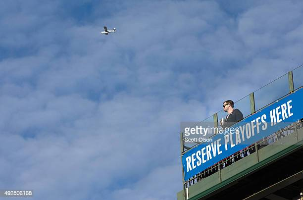 A fan watches from a rooftop across from Wrigley Field as the Chicago Cubs play the St Louis Cardinals in game four of the NLDS championship series...