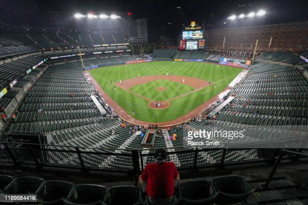 A fan watches play between the Tampa Bay Rays and the Baltimore Orioles during the fifth inning after the game resumed after a rain delay at Oriole...