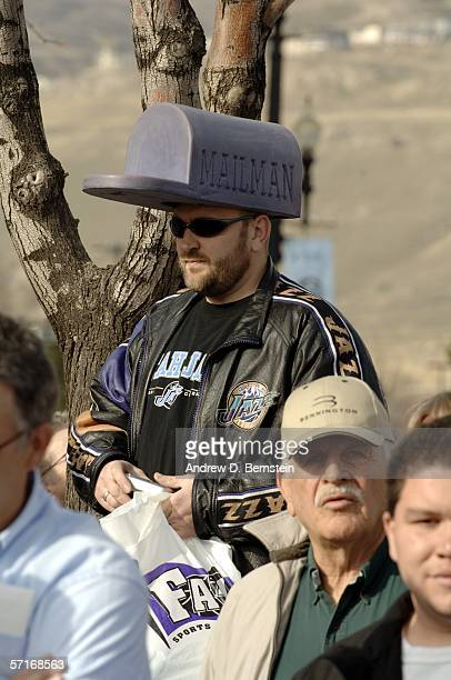 A fan watches retired power forward Karl Malone speak at the unveiling his statue commissioned by Utah Jazz owner Larry H Miller on March 23 2006 at...