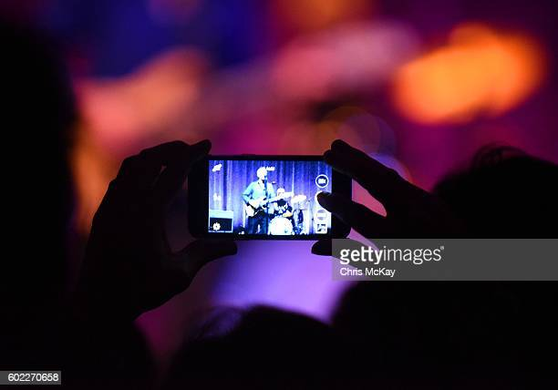 A fan watches Television's Tom Verlaine perform through their cell phone camera at Georgia Theatre on September 10 2016 in Athens Georgia