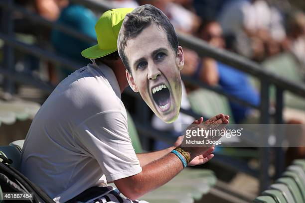 A fan watches the action wearing a Pospisil mask as Julian Knowle of Austria and Vasek Pospisil of Canada talk tactics in their first round doubles...