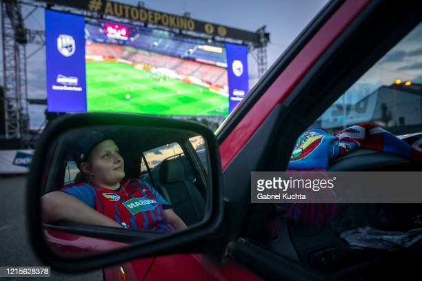 A fan watches the Czech first division football match between FC Viktoria Plzen and AC Sparta Praha at a drivein movie theater on May 27 2020 in...