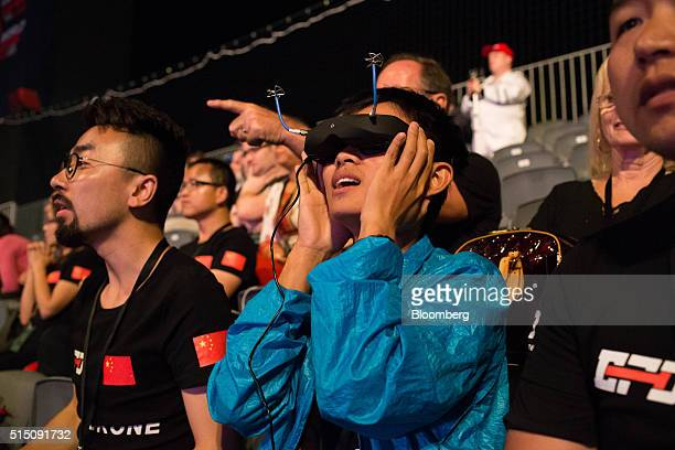 A fan watches the race through her 'first person view' or 'point of view' goggles during the first day of finals at the World Drone Prix drone racing...