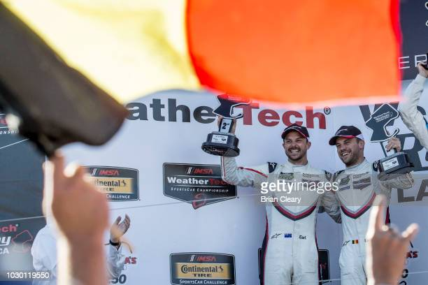 A fan waves a Belgian flag as Laurens Vanthoor of Belgium R and Earl Bamber of New Zealand celebrate their podium finish in the American Tire 250...