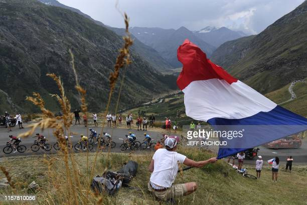 A fan waves a big French national flag as France's Julian Alaphilippe wearing the overall leader's yellow jersey and cyclists ride uphill during the...