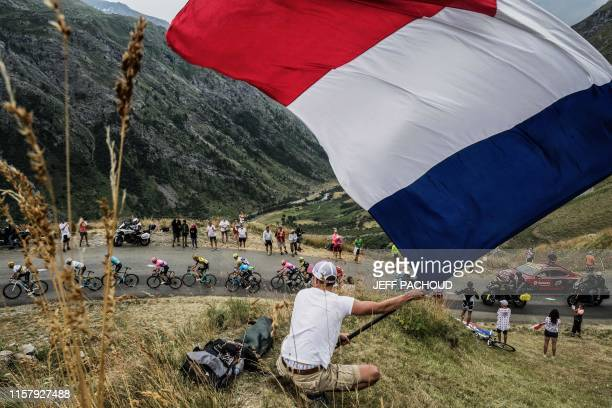 TOPSHOT A fan waves a big French national flag as the pack rides uphill during the nineteenth stage of the 106th edition of the Tour de France...