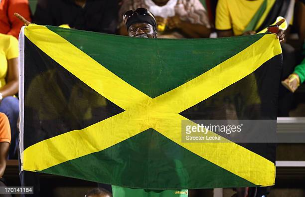 A fan waves a flag before the USA takes on Jamaica in the FIFA 2014 World Cup Qualifier at National Stadium on June 7 2013 in Kingston Jamaica