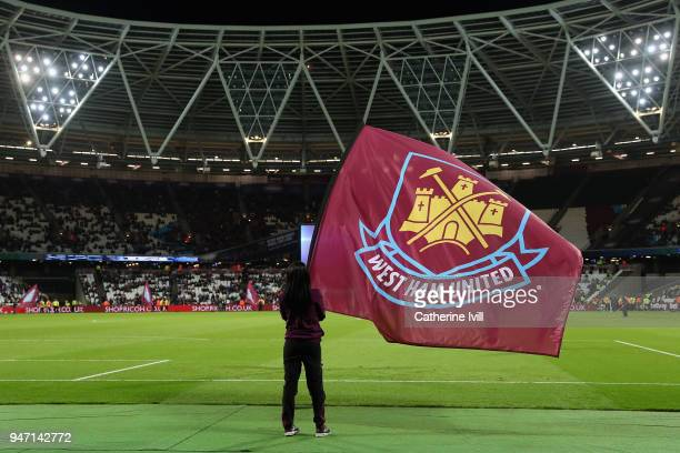 A fan waves a flag during the Premier League match between West Ham United and Stoke City at London Stadium on April 16 2018 in London England