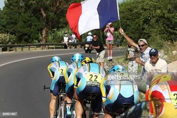 Fan waves a French flag as Kazakh cycling team Astana 's riders compete on July 7, 2009 in the 39 km team time-trial and fourth stage of the 2009...