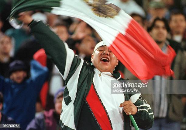 A fan waves a Mexican flag during the 1998 CONCACAF Gold Cup soccer match between Mexico and Trinidad and Tobago in Oakland California 04 February...