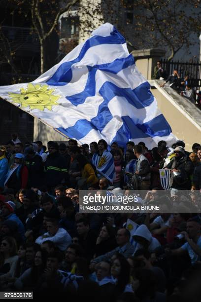 A fan waves a Uruguayan national flag as people gathered at Montevideo's City Hall explanade to watch the FIFA World Cup match between Uruguay and...
