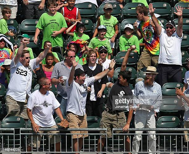 A fan waves after catching the home run ball hit by Alex Rios of the Chicago White Sox of the Minnesota Twins at US Cellular Field on July 25 2012 in...