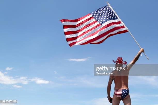 A fan waves an American Flag in the infield prior to the Monster Energy NASCAR Cup Series Coke Zero Sugar 400 at Daytona International Speedway on...