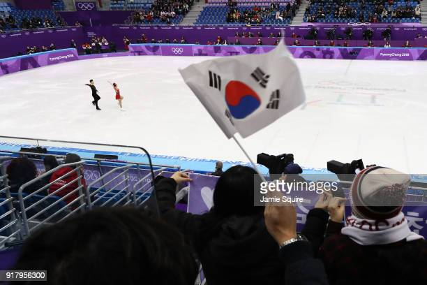 A fan waves South Korean flags as Kyueun Kim and Alex Kang Chan Kam of Korea compete during the Pair Skating Short Program on day five of the...