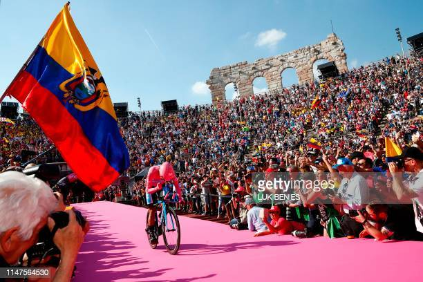 Fan waves the flag of Ecuador as overall race winner Team Movistar rider Ecuador's Richard Carapaz reacts as he enters the arena after competing in...