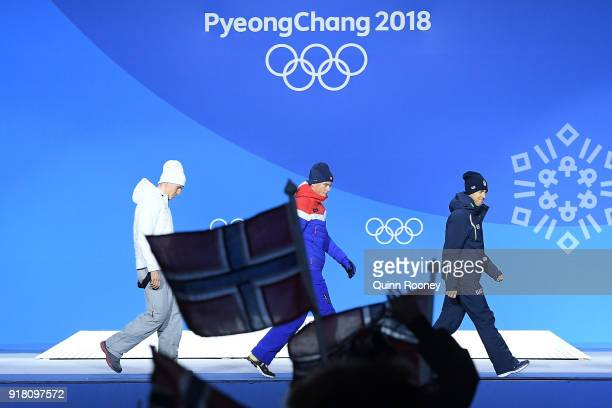 A fan waves the flag of Norway as bronze medalist Alexander Bolshunov of Olympic Athlete from Russia gold medalist Johannes Hoesflot Klaebo of Norway...