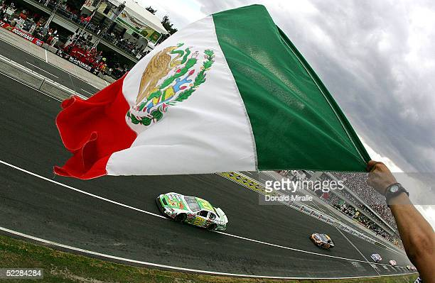 Fan waves the Mexican flag as Kevin Harvick drives his Pelon Pelo Rico Chevrolet Monte Carlo at the start of the Telcel Mexico 200 Nascar Busch...