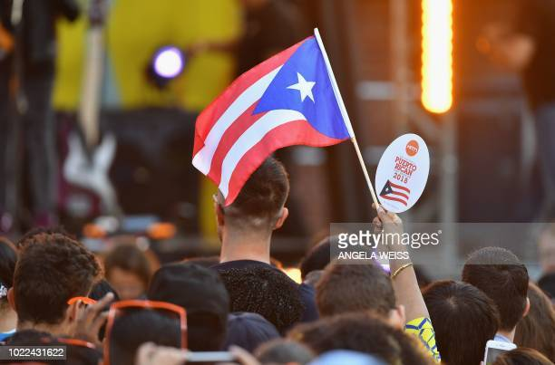 A fan waves the Puerto Rican flag as singer Luis Fonsi performs on ABC's Good Morning America at Rumsey Playfield Central Park on August 24 in New...